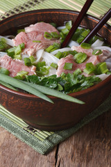 Asian soup with meat, rice noodles and fresh herbs. Vertical