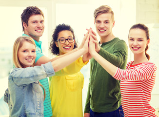 five smiling students giving high five at school