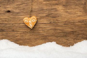 Hängender Lebkuchen mit Schnee auf Holz