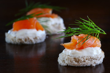 canapes with salmon, cream and dill garnish, on dark brown wood,