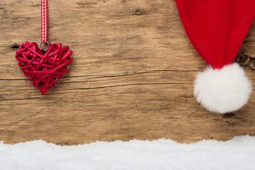 Rotes Herz und Weihnachtsmütze vor Holzhintergrund mit Schnee