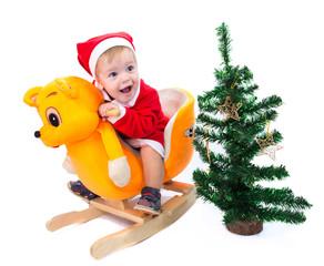 Little boy in Santa Claus suit riding a toy cat