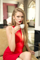 Pretty blonde woman wearing red dress and having coffee