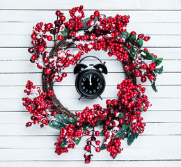 Holly christmas wreath with clock on wooden table.