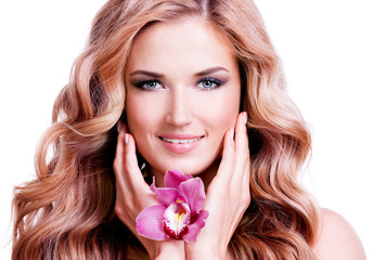 Beautiful young smiling woman with flower near face.