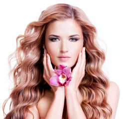 Beautiful young woman with flower near face.