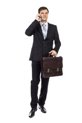 Handsome young business man holding a suitcase and talking on ph