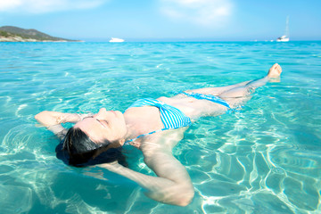 A beautiful girl relaxes in a heavenly sea, Saleccia beach Corsi