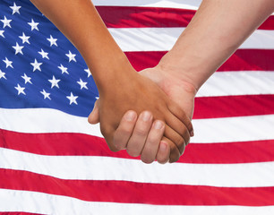close up of hands holding over american flag