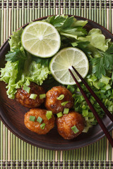 fish balls in curry sauce with lime top view vertical