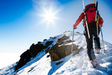 Climber walking up along a steep snowy ridge with the skis in t - 74050739