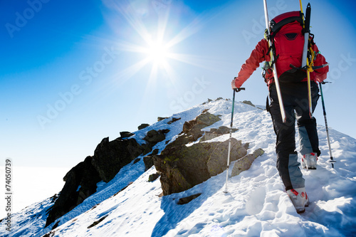 Climber walking up along a steep snowy ridge with the skis in t