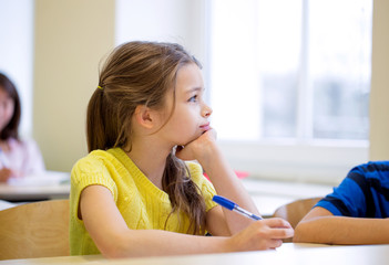 school girl with pen being bored in classroom