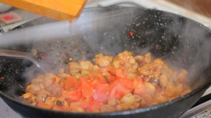 Making a traditional spanish paella. Adding tomato.