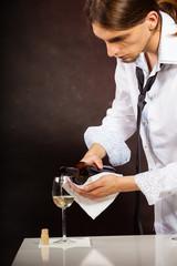 Man waiter pouring white wine into glass.