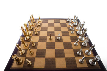 Chess match underway with gold and silver pieces.