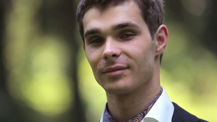 Portrait of young handsome groom on the nature