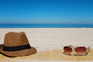 Hat and sunglasses on a beach in summer