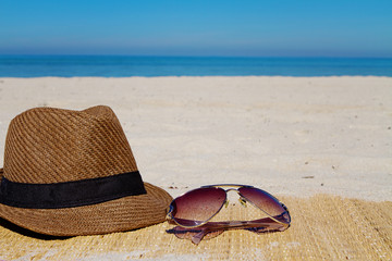 Summer fashion hat and sunglasses on a beach