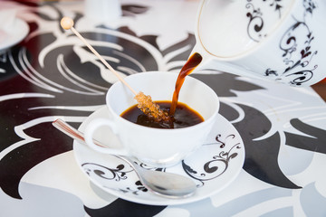 Coffee from a beautiful black and white teapot