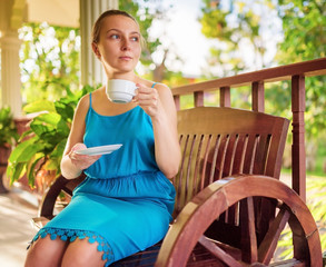 Young woman in blue dress enjoying a cup of beverage