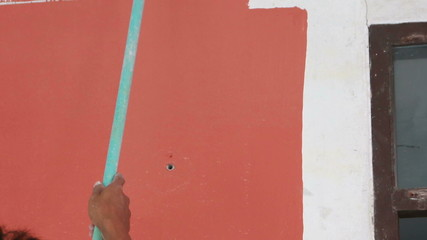 Roller Painting Red color on the wall
