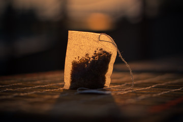 Tea bag on wooden table in sunshine