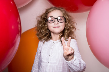 Young girl in glasses showing two fingers victory against the ba