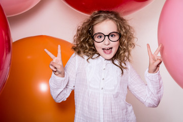 Young girl in glasses showing two fingers victory