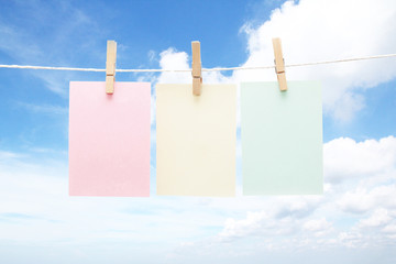 Three colorful notes on wooden pegs with blue sky background