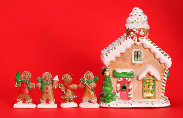 Gingerbread house and people over red background