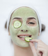 Beautiful young woman receiving facial mask of cucumber in beaut