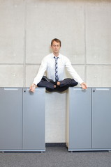 businessman v3.0 - meditating in lotus pose  in office