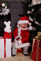 crying baby Santa Claus by the fireplace