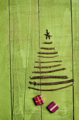 Christmas tree arranged from sticks, wooden green background