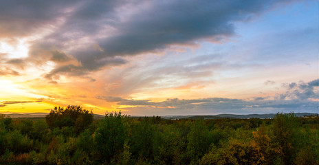 Summer sunset over the hills covered with forest