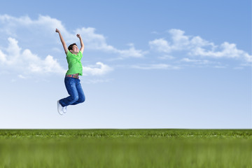 Young boy is jumping in nature on green grass