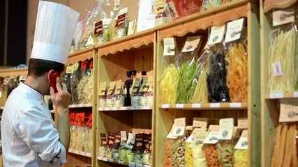 chef phone in front of colourful pasta in bags in shelf