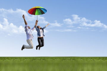 Happy young couple is flying with umbrella on nature
