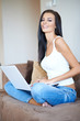 Pretty Young Woman in Sitting on Couch with Laptop