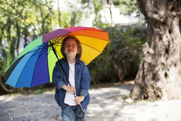 Lovely oung boy with umbrella in garden