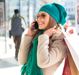 Young women in shopping, talking by phone