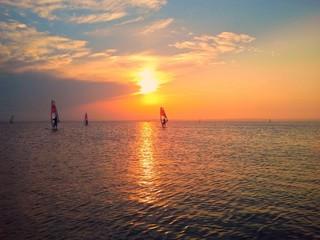 Windsurfers in the sea with sun set