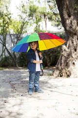 Young boy with umbrella in garden