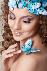 attractive young woman with curly hairstyle and blue butterflies