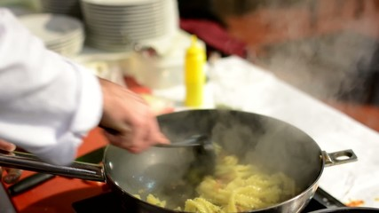 chef prepares food - chef cook pasta on frying pan
