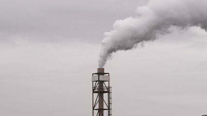 Industrial chimney emitting pollution smoke in cloudy sky