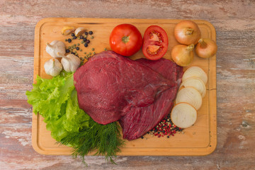 raw beef meat with vegetables on wooden plate