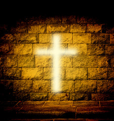 Christian religious cross with gold light on the brick wall