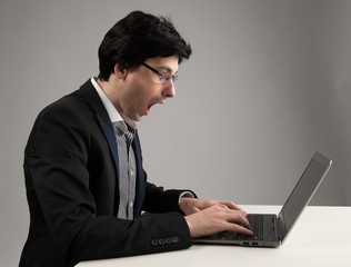 shocked businessman staring at his laptop